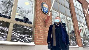 En man i vinterkläder står utanför en byggnad. På väggen finns ett emblem där det står Sveriges konsulat.