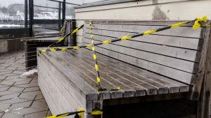 Grov träbänk som stängts med svartgula plastband.