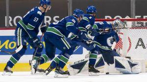 Några Vancouver-spelare framför den egna målvakten.
