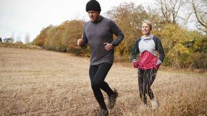 Man och kvinna joggar på åker