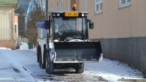 Juuso Sahlberg kör en liten traktor som sandar en trottoar