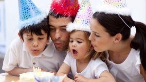 En familj som blåser ut ljus på en tårta.