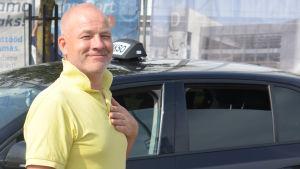 Taxichauffören Peep står vid sin taxi med handen på hjärtat