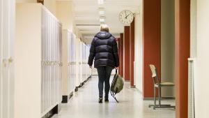 En ensam flicka med ryggen vänd mot kameran går i skolkorridor
