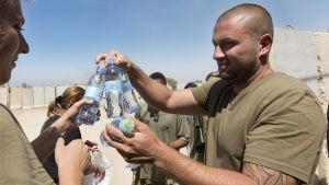 Israelisk soldat delar ut vatten till sina kamrater nära gränsen till Gaza
