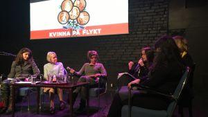 Paneldeltagare vid ett bord. Bakom en logo med orden Kvinna på flykt.