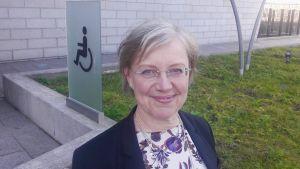 Maija Sakslin står vid en invaskylt.