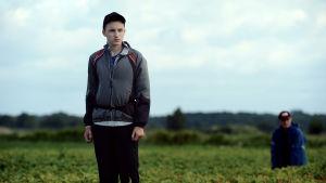 Wojtek (Stanislaw Cywka) står mitt i jordgubbsåkern och tittar mot horisonten.