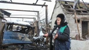 En kvinna i byn Novoluganskoje, i Donetsk, visar upp sitt skadade garage efter granatbeskjutning den 20 december.