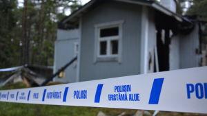 Polistejp runt ett eldhärjat hus.