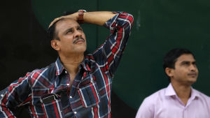 En man följer med bekymrad min med tavlorna som visar kursutvecklingen på börsen i Bombay, Indien.