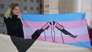 Elsa Tauria håller i en blå, rosa och vit banderoll med en bild av ett svart vapen som bryts i två delar.