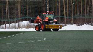 En traktor kör bort snö från sidorna av den uppvärmda konstgräsplanen i Karis den 6 mars 2018.