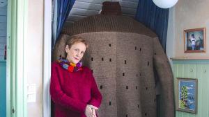 Kuvittaja Virpi Talvitie poseeraa suuren villapaidan edessä.