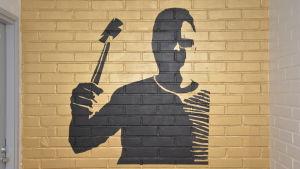 En väggmålning i Karjaan yhteiskoulu som föreställer en man med en hammare.