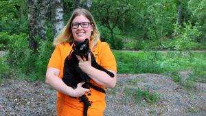 En svart katt i famnen på en ung kvinna.