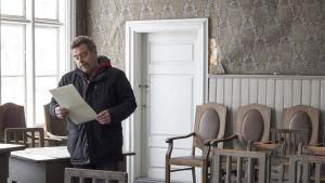 En man står i ett gammal hus. Det är ett stort rum med gamla buckliga tapeter. Längs med väggen står gamla stolar av trä. Han läser på ett papper.