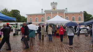 Folkmassa på Lovisa torg i regnigt före