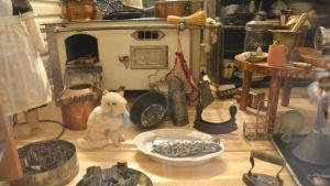 Vy inifrån ett dockhus. Små möbler och en katt.