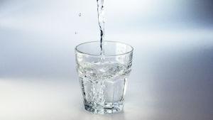 Vatten som rinner i ett glas mot en neutral vit bakgrund.