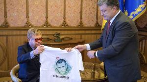 Ukrainas president Petro Porosjenko håller upp en t-skjorta med en bild av den fängslade Oleg Semtsov inför den brittiska musikern Elton John i Kiev i september 2015.