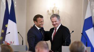 President Sauli Niinistö ryggdunkar Frankrikes president Emmanuel Macron.