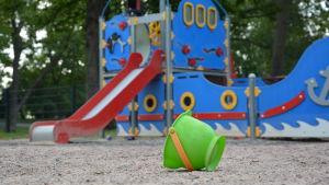 En grön bunke omkullfälld framför en rutschbana i en lekpark.