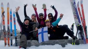Fem kvinnor iklädda tjocka vinterkläder. Sitter och hurrar och vifta med Finlands flagga. De befinner sig på Grönland, i ett snölandskap.