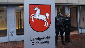Poliser står utanför domstolsbyggnaden i Oldenburg där rättegången mot den misstänkta massmördaren inleddes