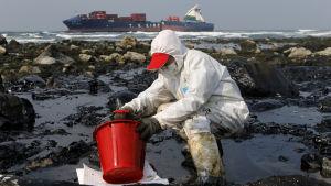 Man i skyddsutrustning som försöker putsa olja bort från stranden i Taiwan.