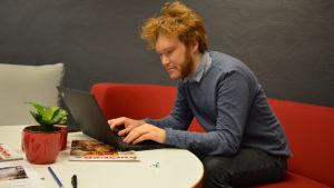 Jakob löfgren, en man med stort och krulligt hår sitter i en röd soffa och skriver på sin bärbara dator.