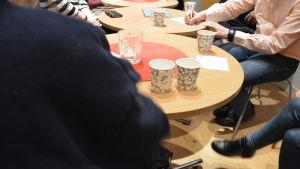 Flera pappersmuggar på tre runda bord, kring vilka personer sitter och pratar. En person har en rosa skjorta.