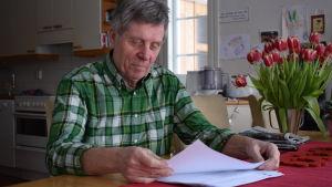 Cay Blomberg sitter med papper i handen vid sitt köksbord. Grönrutig skjorta på sig och en bukett tulpaner på bordet.
