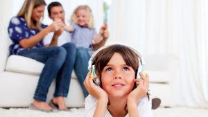 Pojke lyssnar med hörlurar i vardagsrum