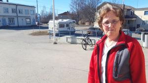 En äldre dam med röd tröja står på en asfalterad gårdsplan. Hon har medellångt mörkt hår och glasögon.