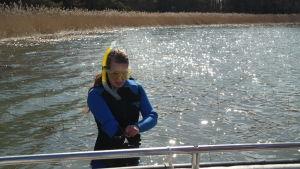 Linda Sandström iförd torrdräkt står i vattnet och bereder sig för snorkling