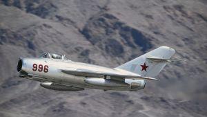 Neuvotoliittolainen hävittäjä MIG-15 lentää taustalla vuoria.