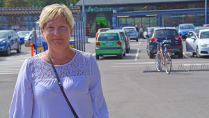 Kvinna står och ler vid matbutik i Borgå.