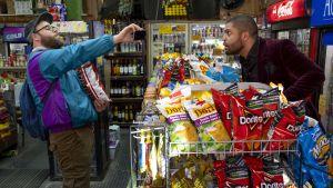 Fred Flarsky (Seth Rogen) och Lance (O'Shea Jackson Jr.) står i en kiosk och pratar.