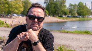 En man iklädd solglasögon och med bister uppsyn pekar på kameran.