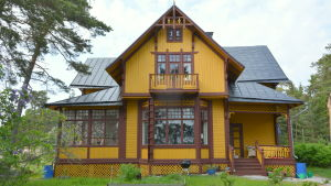 Det gula trähuset på Runsala har brunmålade knutar och detaljer.