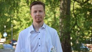 En man (läkare) i vit läkarrock poserar utomhus. Ser rakt in i kameran. Sommar.