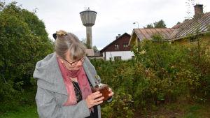 """Ann-Sophie tittar i en kaffekvarn hemma på sin gård. Huset """"Berthas"""" och Nykarleby vattentorn syns i bakgrunden."""