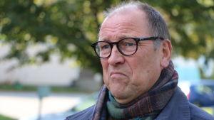 En skallig man med runda glasögon ser sur ut.