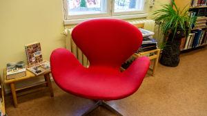 Röd stol i bibliotek.