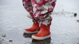 Barn i regnkläder står i vattenpöl