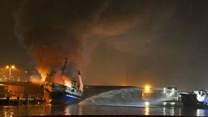 Brinnande fartyg i hamn under pågående släckningsarbete.