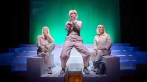 Tre skådespelare i vitt på trappstegsliknande vita kulisser mot en turkos fond. Skådespelaren i mitten Cecilia Paul står bredbent som om hon sjöng i en mikrofon.