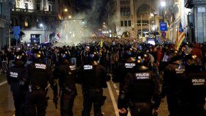 Flera kravallpoliser står med blicken riktad mot hav av demonstranter i centrala Barcelona.