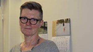 En kvinna med glasögon, kort hår. Bakom, på väggen, hänger en väggkalender.